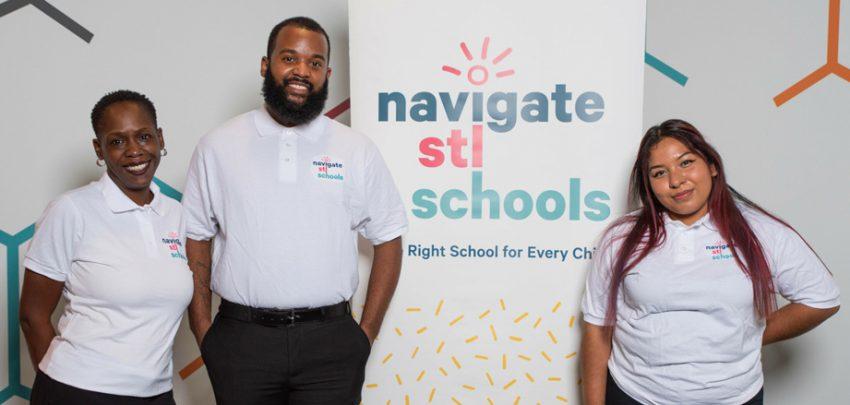 Three school navigators posed in front of Navigate STL Schools banner